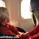 Baby or toddler flying on airplane in red christmas PJs