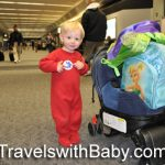 toddler at the airport for holiday travel in red pajamas from travelswithbaby.com