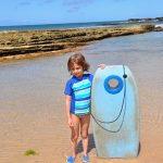 Little kid with looky board at Salt Pond Park in Kauai