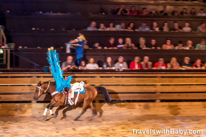 Male trick rider upside down on horse at Dolly Parton's Stampede
