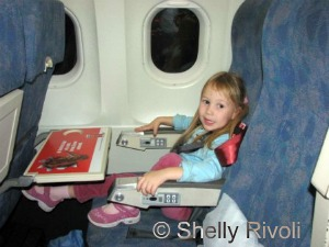 Child using CARES harness with tray table, window www.travelswithbaby.com
